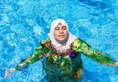 68275333-muslim-arabic-woman-with-burkini-in-pool
